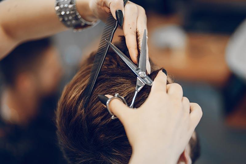 coiffeuse coupant les cheveux d'un homme